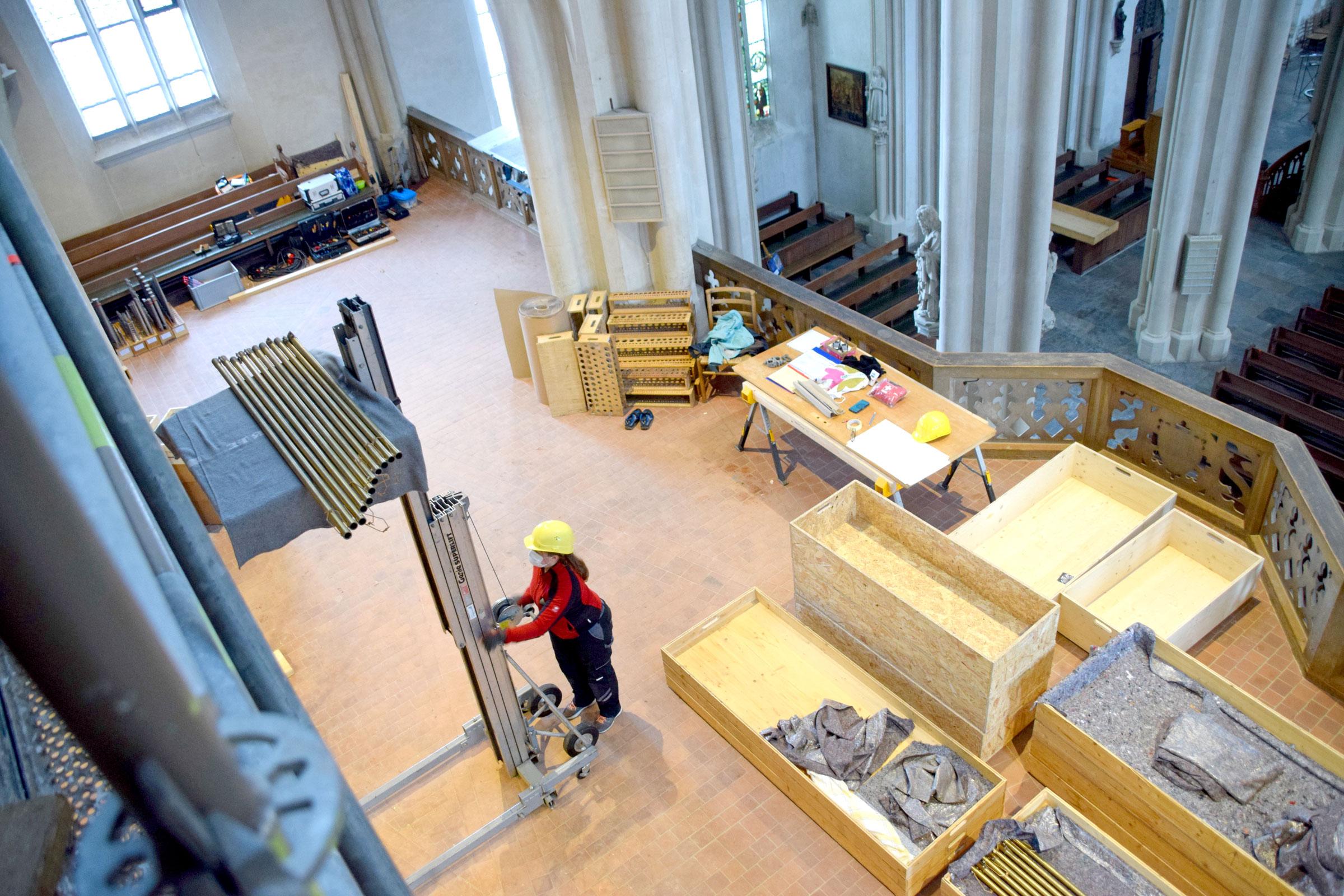 Julia Bender von der Firma Sandtner holt mit dem handbetriebenen Aufzug die abgebauten Pfeifen der Orgel auf die Empore. Hier werden sie verpackt und per zweitem Aufzug abtransportiert. Foto: am