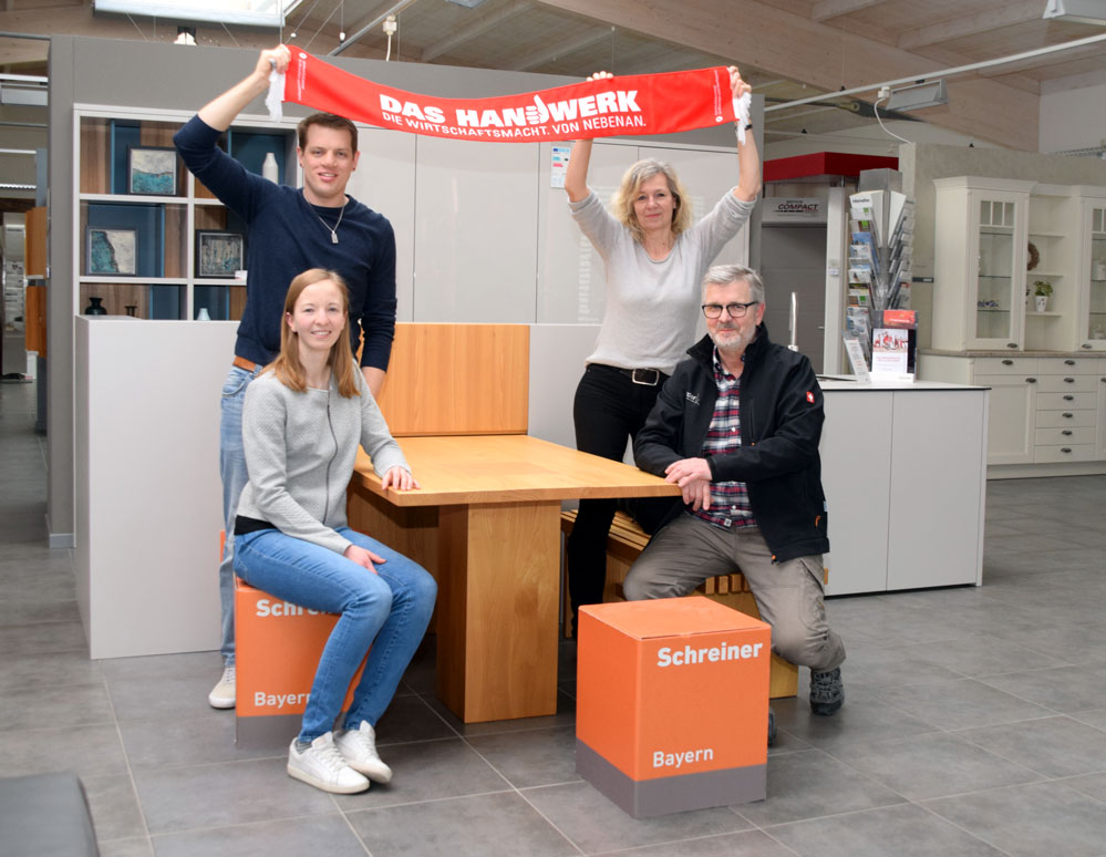 Stefan Berndlmaier und Claudia Korder halten den Meisterschal von Laura Korder hoch. Rainer Korder freut sich, dass der Betrieb nun in die vierte Generation geht. Foto: am