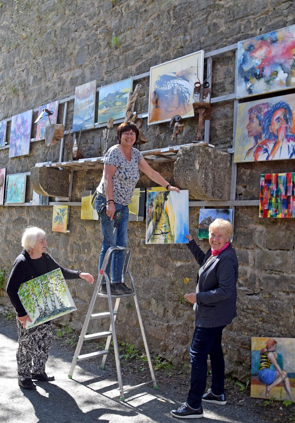 """Von links: Ingeborg Goebel, Helga Fabi und Ruth Bücker, engagierte Kunstkreismitglieder, kümmern sich um das Gelingen der """"Kunstmauer"""". Foto: am"""